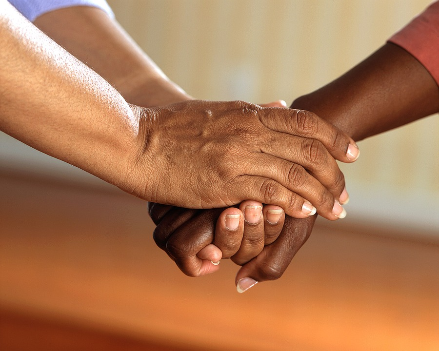 A person holds another person's hands in theirs showing support